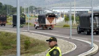 Lorries with humanitarian aid drive past a Colombian policeman to the Tienditas Bridge on the border between Colombia and Venezuela. Photo: 7 February 2019
