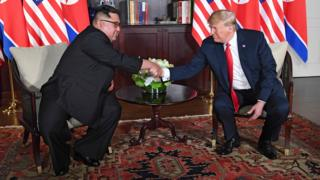 US President Donald Trump (R) shakes hands with North Korea's leader Kim Jong-un (L) as they sit down for their historic US-North Korea summit
