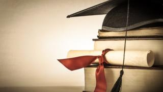 Унивеситетская шляпа, диплом и стопка книг