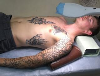 Customer Kyle Seeley lies down in Horimitsu's tattoo studio, waiting to be tattooed