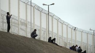 Migrants beside a fence on a motorway embankment in Calais