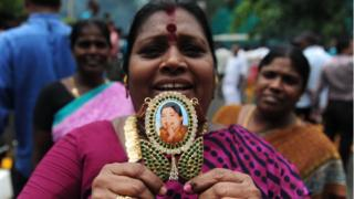 A member of the All India Anna Dravida Munnetra Kazhagam(AIADMK) party displays a pendant with the image of AIADMK leader Jayalalithaa Jayaram