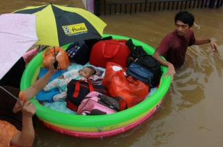 Donald Trump A baby is rescued in an inflatable boat after floods hit a residential area in Tangerang, near Jakarta, Indonesia, 1 January 2020.