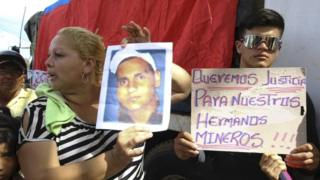 """""""We want justice for our miner brothers,"""" reads the sign held at a demonstration in Tumeremo."""