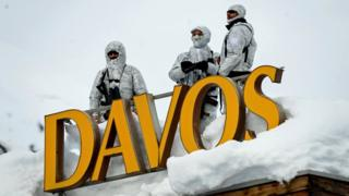 "Armed security personnel stand guard on the rooftop of a hotel, next to letters reading ""Davos"""