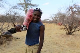 Hadza man carrying zebra leg
