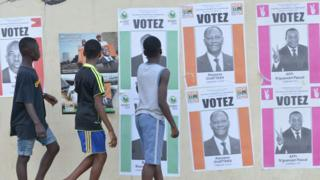 Boys walk past Ivory Coast's presidential election candidate campaign posters on October 14, 2015 in Cocody, Abidjan