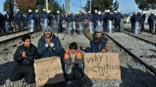 Greek police officers stand guard behind two men and two children demonstrating between railway tracks as they wait with other migrants and refugees to cross the Greek-Macedonian border near Idomeni on 7 December