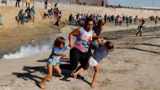 A migrant woman, Maria Meza, holds onto two of her daughters as she escapes the tear gas