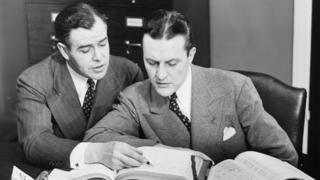 Black-and-white picture of two men checking accounting books