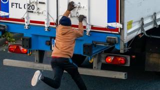 man tries to climb on lorry