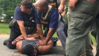 Suspect Willie Cory Godbolt held to the ground by police