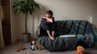 a sad woman sits on a sofa