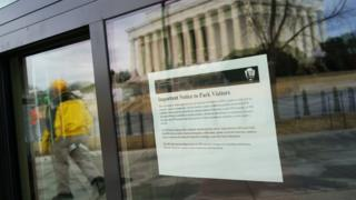 An image of the Lincoln Memorial is reflected onto a window of an information kiosk with a notice regarding the government shutdown in Washington, DC on January 22, 2018.