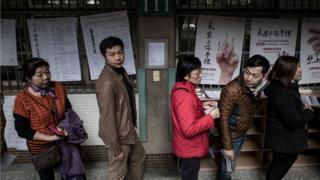 Voters queue up at a polling station in New Taipei City on January 16, 2016