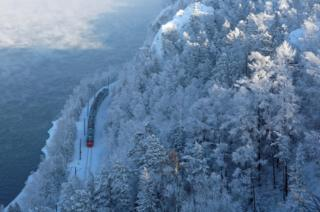 A passenger train moves along the bank of the Yenisei River in the Siberian Taiga forest, which is covered with snow and hoarfrost outside Krasnoyarsk, Russia, 11 February 2019.