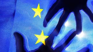 The silhouette of hands behind a European Union flag