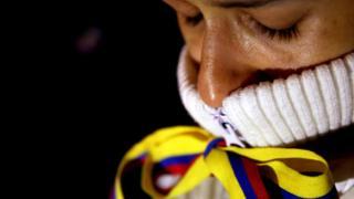 Mujer con lazo en la boca con los colores de la bandera de Colombia.
