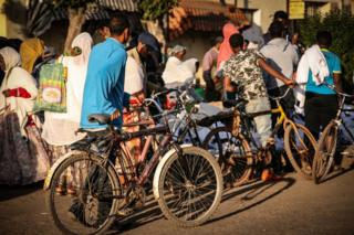 People with bicycles walking past street stalls in Asmara, Eritrea