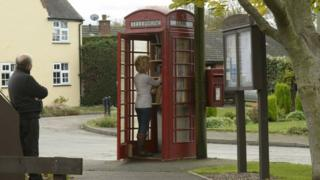 Wendy Hanlon looks at books in the red phone box