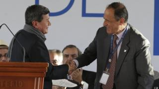 Colombia's government representative Juan Camilo Restrepo, right, shakes hands with National Liberation Army (ELN) representative Pablo Beltran during a ceremony marking the start of formal peace talks in Quito, Ecuador,