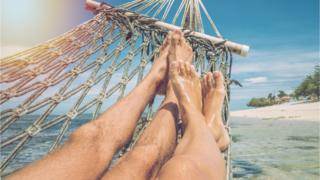 A couple lie in a hammock on an Indinesian beach
