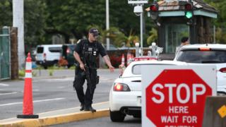 A guard armed with an assault rifle checks vehicles entering the Nimitz Gate entrance of Joint Base Pearl Harbor Hickam