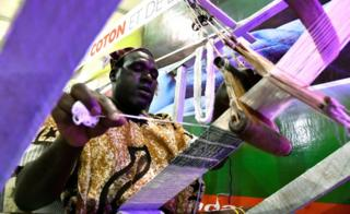 An weaver works on a loom at the opening of the fourth International Exhibition of Agriculture and Animal Resources (SARA 2017) in Abidjan on November 17, 2017