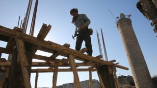 عامل عراقي ينصب حمالات خشبية