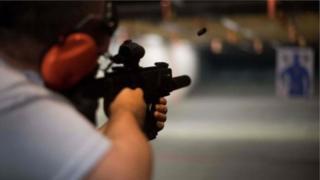 Homem com fuzil em estande de tiro