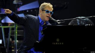 British singer-songwriter Elton John performs with his band during a concert in Gijon, July 17, 2015
