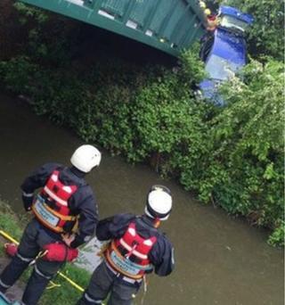 Crashed car hanging over canal bridge