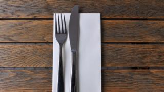 A knife, fork and napkin on a wooden table