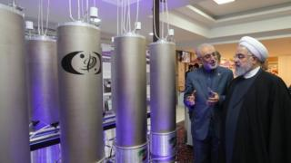 "Iranian President Hassan Rouhani (2nd L) listening to head of Iran's nuclear technology organisation Ali Akbar Salehi (R) during the ""nuclear technology day"" in Tehran on 9 April."