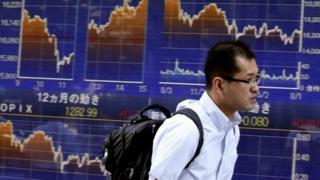 Man walks past Tokyo stock market board