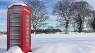 A telephone box in a snow scene