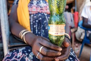 A woman holds a plastic bottle filled with locusts