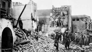 Indian soldiers walking through the debris of a building in Amristar in August 1947