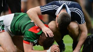 A Mayo player is consoled by a Dublin player after the 2017 final