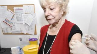 Old woman being getting the jab