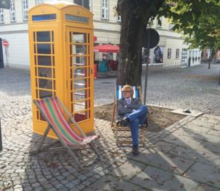 John Byford sitting next to a yellow phone box