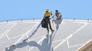 A protester on top of the Sydney Opera House sails is approached by a policeman