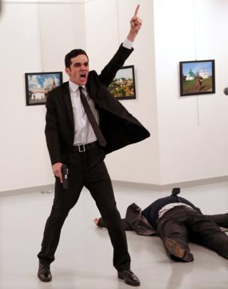 турецький поліцейський Мевлут Мерт Алтінтас з пістолетом в руці, через кілька секунд після того, як він застрелив посла.