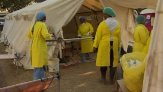Health workers carry a stretcher into a tent