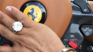 Anthony Gignac shares a photo of his hand, adorned in a large ring, resting against the wheel of his ferrari