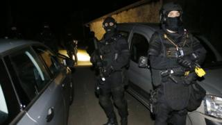 French police officers stand outside a house during a search operation in Louhossoa, south-western France, Friday, Dec 16, 2016