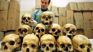 Bosnian pathologist Rifat Kesetovic examines skulls of victims taken from mass graves and in wooded areas following the 1995 massacre