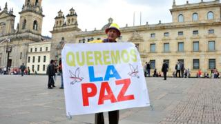 """Man holds a sign reading """"We want peace"""" outside the Colombian Senate in Bogota, on November 29, 2016"""