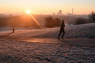 A jogger running up a frost-covered path