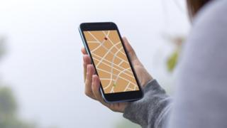 Young woman using GPS map direction on smartphone app.
